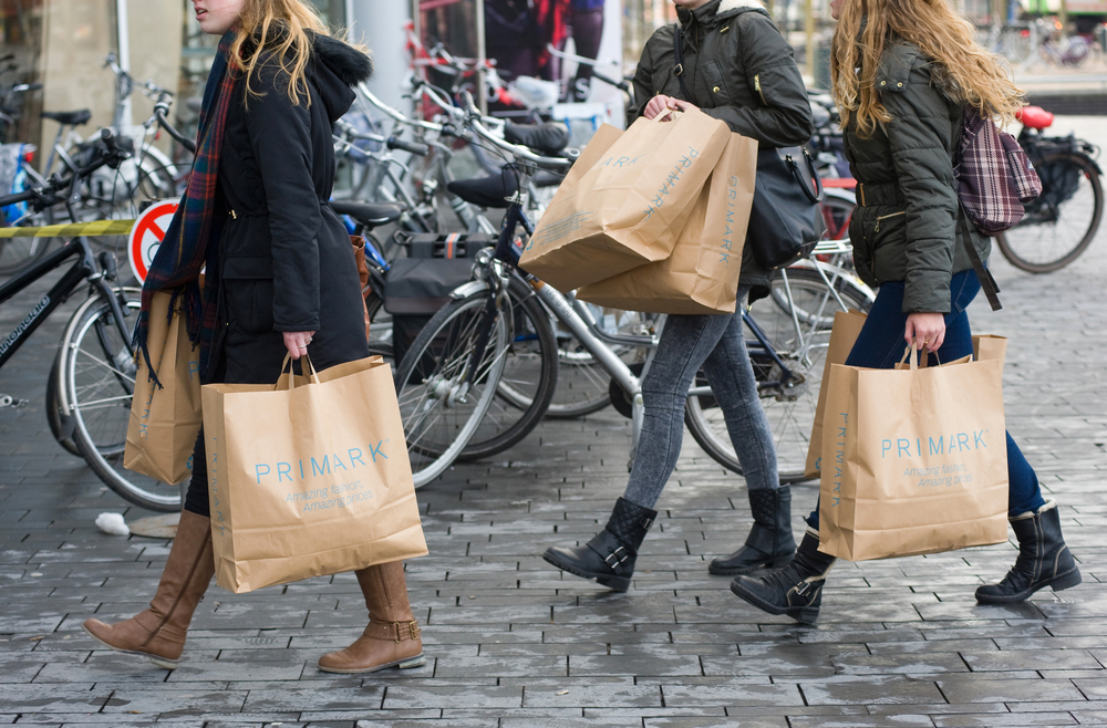 ENSCHEDE, THE NETHERLANDS - 05 FEB, 2015: Three women with shopping bags from Primark warehouse are walking on the street
